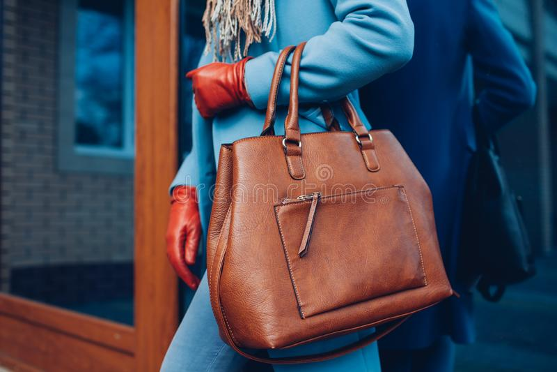 Beauty and fashion. Stylish fashionable woman wearing coat and gloves ,holding brown bag handbag stock image