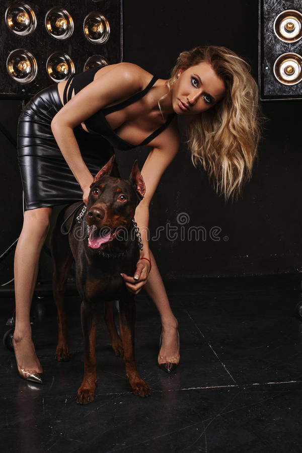 Beauty and fashion. Woman with gorgeous curly hair embraces the Doberman. Dark background, the girl next door with a dog royalty free stock photography