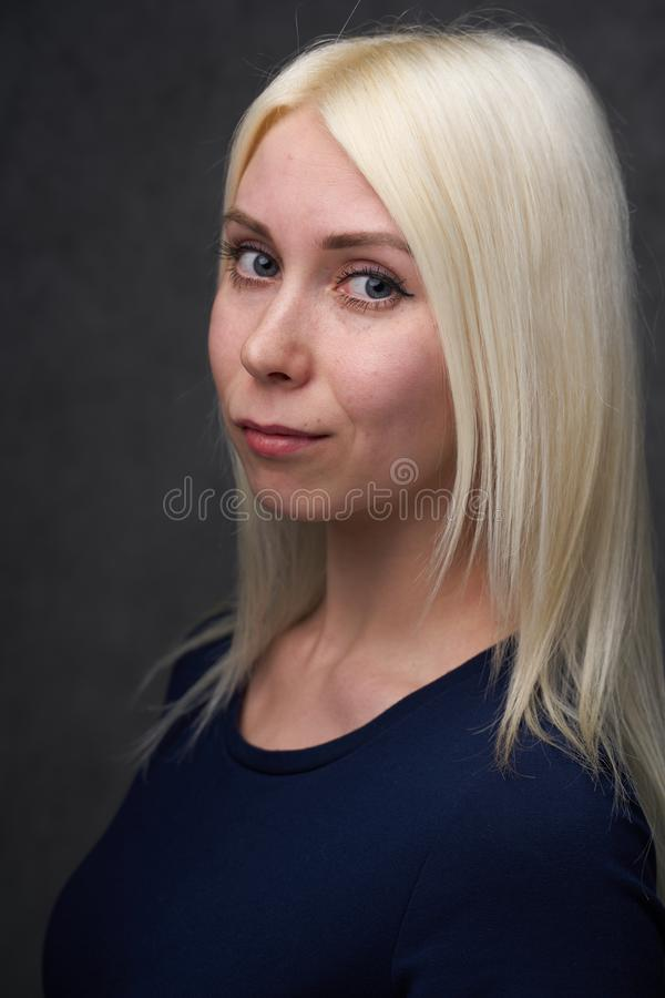 Beauty female blond in black casual clothes on gray background. Portrait royalty free stock images