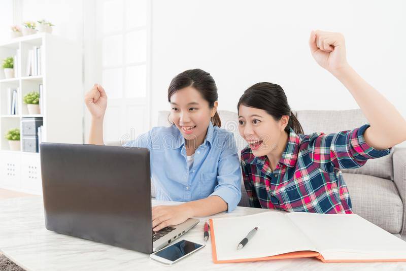 Beauty female friends studying together at home. Young beauty female friends studying together at home and looking at mobile computer raised hand up to celebrate stock photos