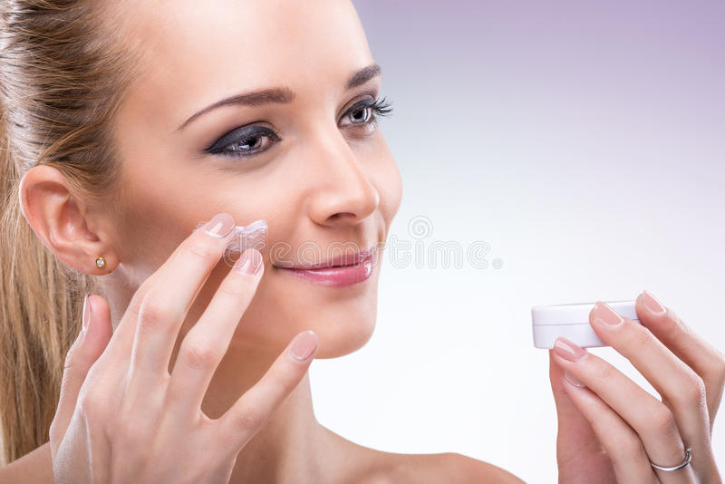 Beauty flawless skinned woman with face cream. stock photography