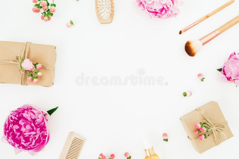 Beauty frame composition of peony flowers with hairbrush, tassel and gifts on white background royalty free stock photo