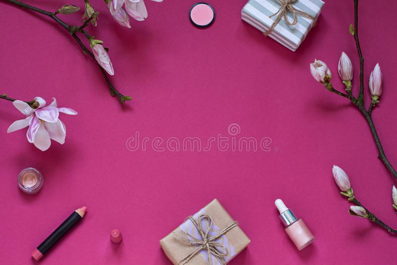 Beauty frame with gifts, cosmetics and magnolia flowers on the purple background. Top view concept composition. stock photo