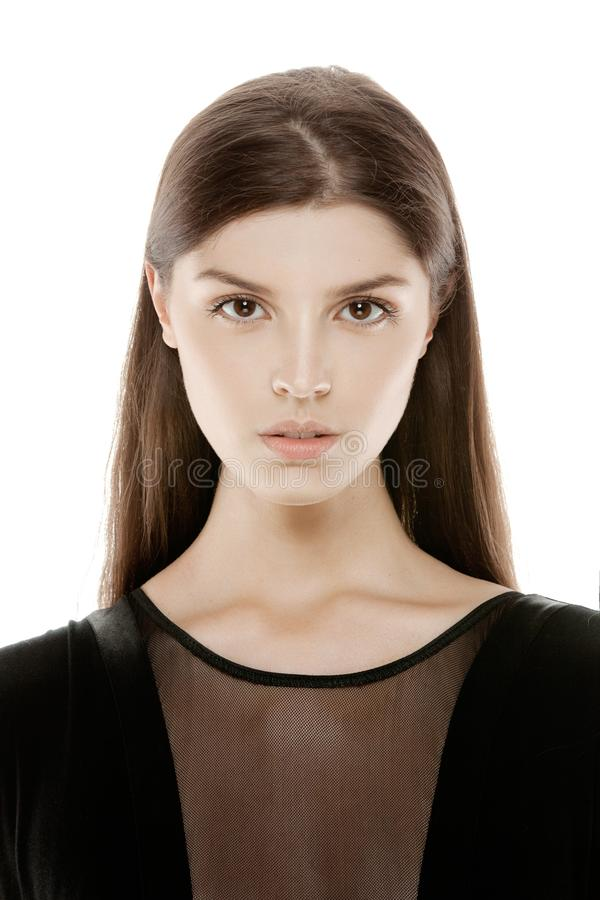Closeup of a young female model in black dress, looking at camera, isolated on a light background. royalty free stock image