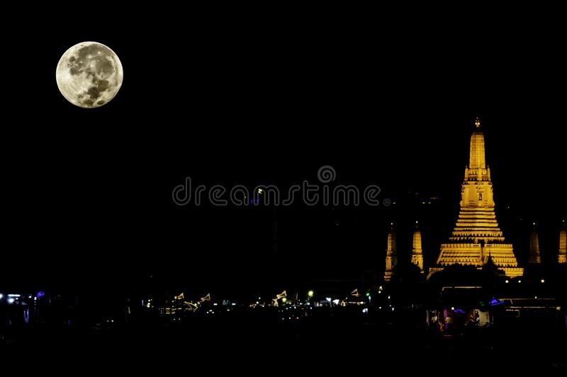 The beauty of the full Moon and Wat Arun at night with gold. stock photography