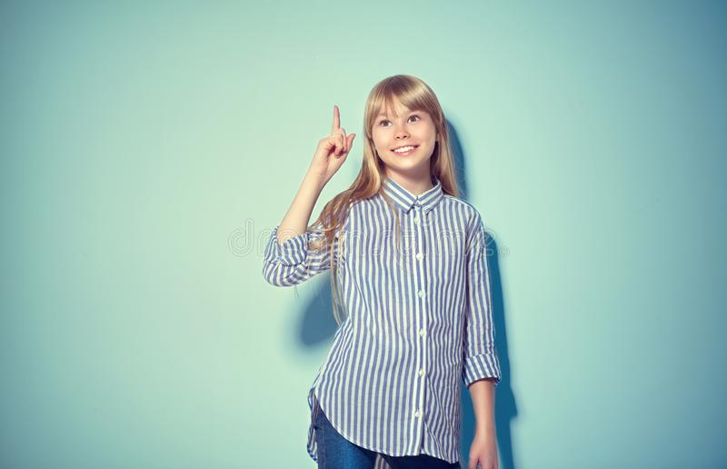 Beauty funny blonde teenage girl has an idea, pointing finger, showing empty copy space for text, blue background. Happy girl presenting point. School girl royalty free stock photo