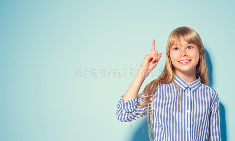 Beauty funny blonde teenage girl has an idea, pointing finger, showing empty copy space for text, blue background. Happy girl presenting point. School girl stock photos