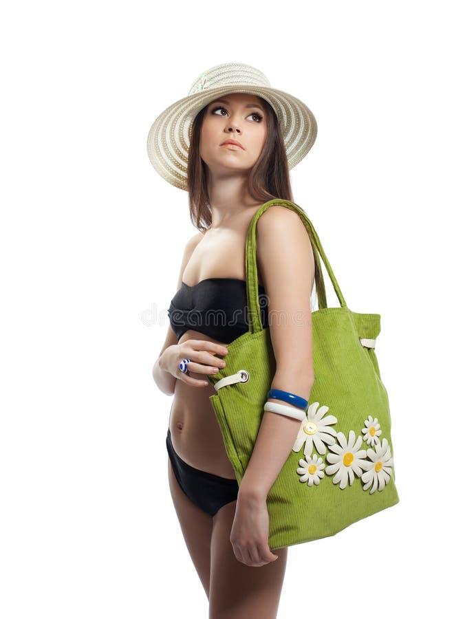 Beauty girl in black bikini with green beach bag royalty free stock image