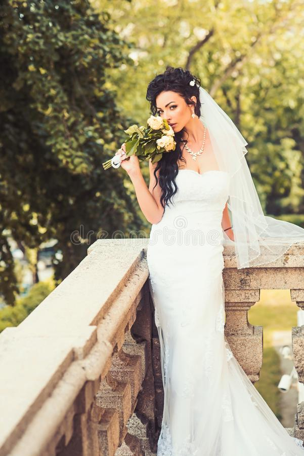 Beauty girl with bridal makeup and hairstyle. Sensual woman with wedding bouquet. Woman with flowers on balcony. Bride. In fashion white dress and veil. Wedding royalty free stock image