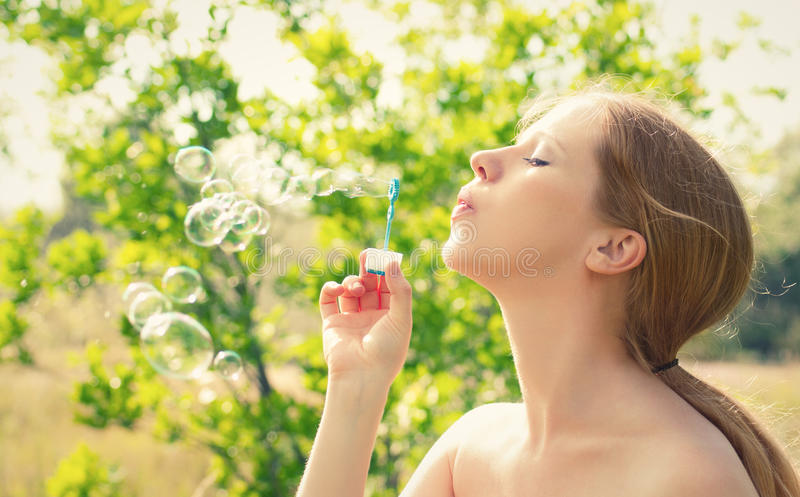 Beauty girl and bubbles on the nature stock photos