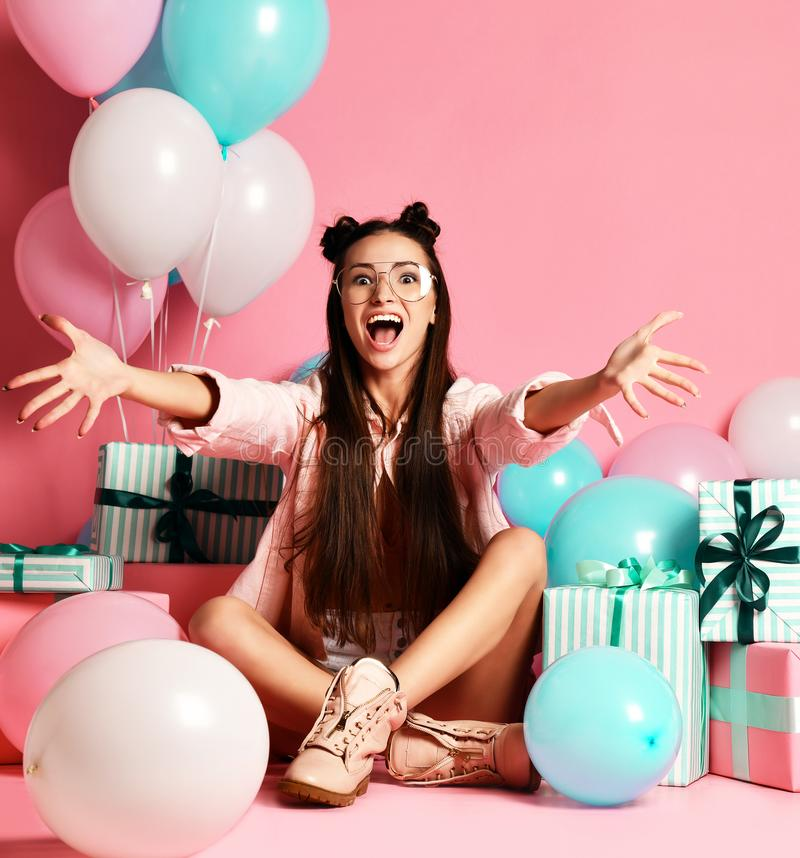 Close-up portrait of attractive girl with present and balloons for studio. royalty free stock photos