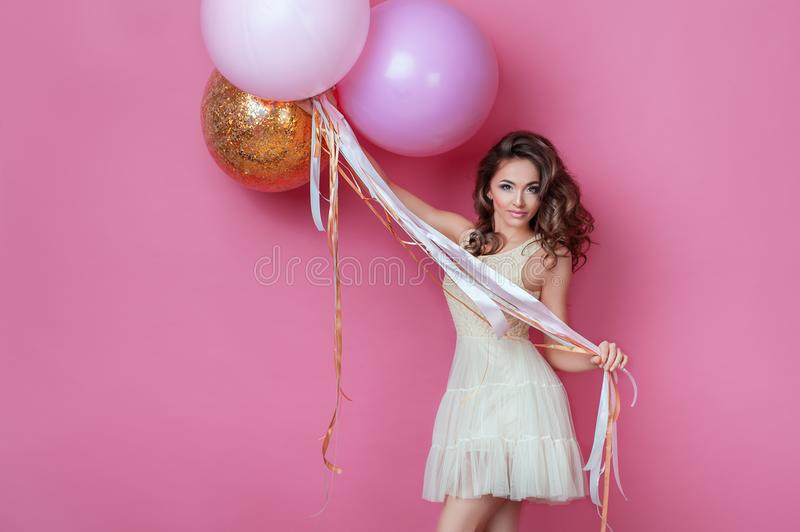 Beauty girl with colorful air balloons laughing over pink background. Beautiful Happy Young woman on birthday holiday party. Fashi stock photos