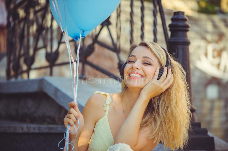 Beauty girl with colorful balloons laughing on city steps. Beautiful happy young woman on a sunny bright day. Joyful model is stock photography