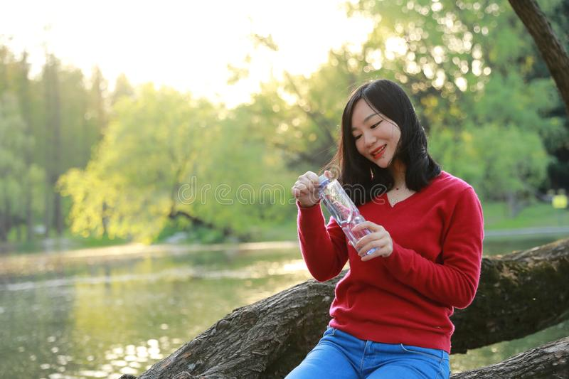 Beauty girl drink water live a healthy balance life in spring autumn park. Portrait of a Asian Chinese free woman reading book sit on a tree by a river in spring stock photography