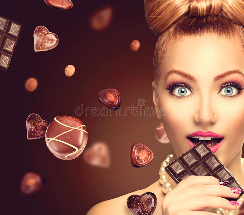 Beauty girl eating chocolate. Beauty fashion model girl eating chocolate stock image