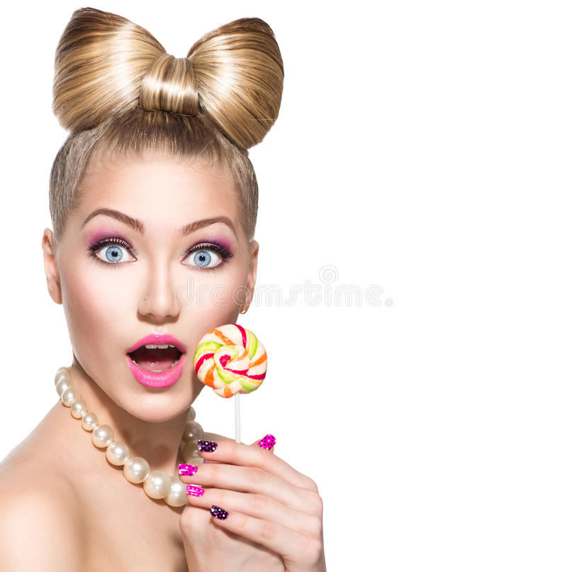 Beauty girl eating colourful lollipop. Beauty fashion model girl eating colorful lollipop over white royalty free stock photos