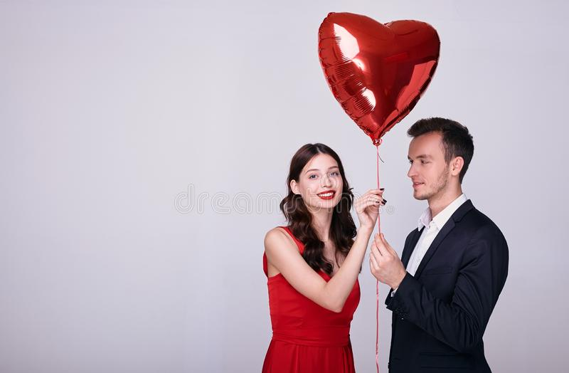 Beauty girl and her handsome boyfriend keeps a heart-shaped balloon stock images