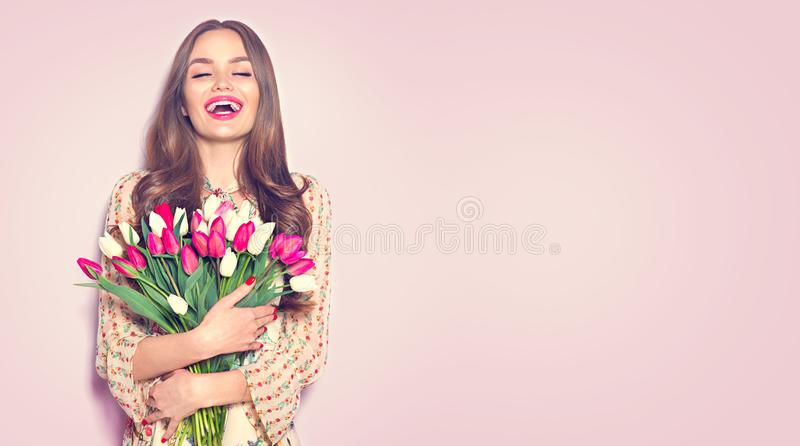 Beauty girl holding spring tulips. Happy beautiful woman receiving a bouquet of colorful tulips stock photo