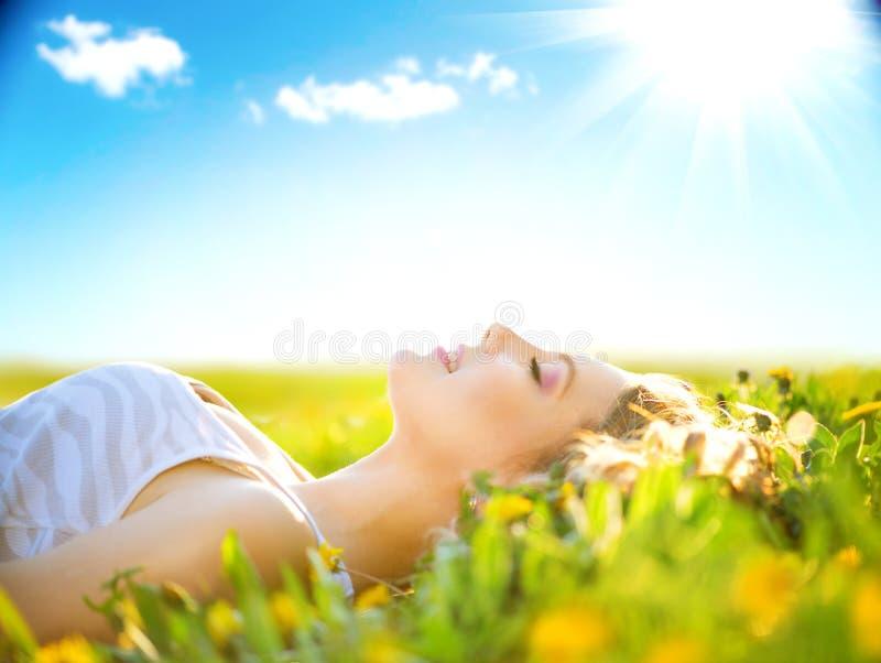 Beauty girl lying on summer field. Beauty romantic girl lying on summer field outdoors royalty free stock images