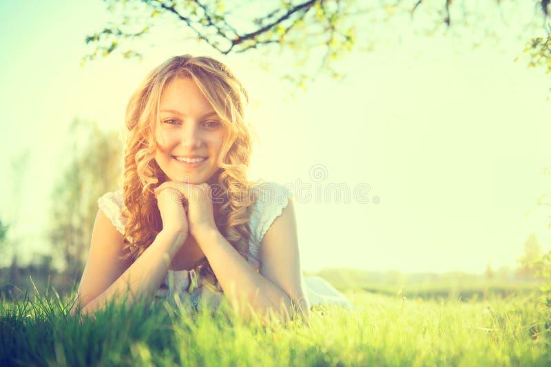Beauty girl lying on summer field. Beauty romantic girl lying on summer field outdoors stock photography