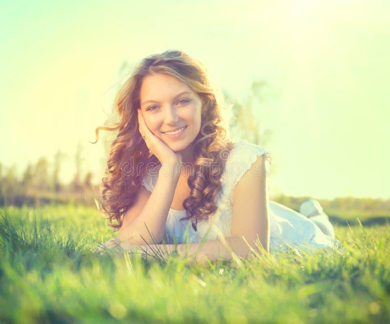 Beauty girl lying on summer field. Beauty romantic girl lying on summer field outdoors stock image
