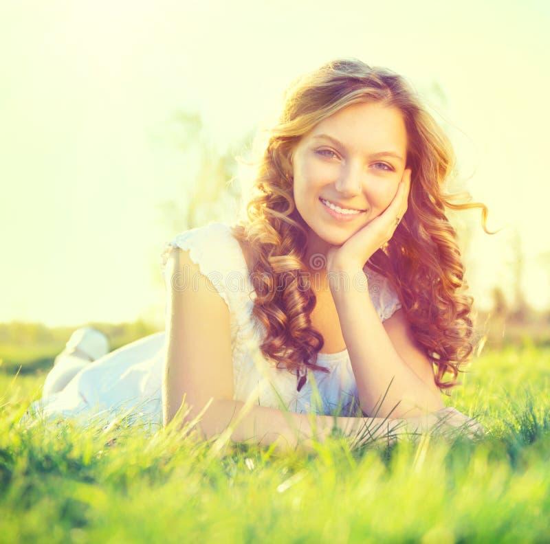 Beauty girl lying on summer field. Beauty romantic girl lying on summer field outdoors stock photo
