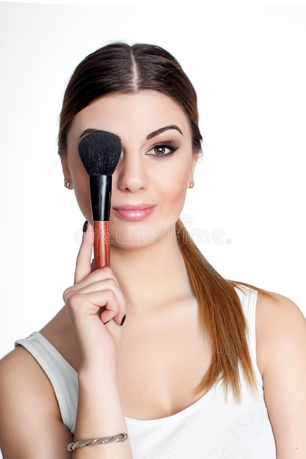 Beauty Girl make up artist with Makeup Brush. Bright Holiday Make-up for Brunette Woman with Brown Eyes. Beautiful Face. Makeover royalty free stock images