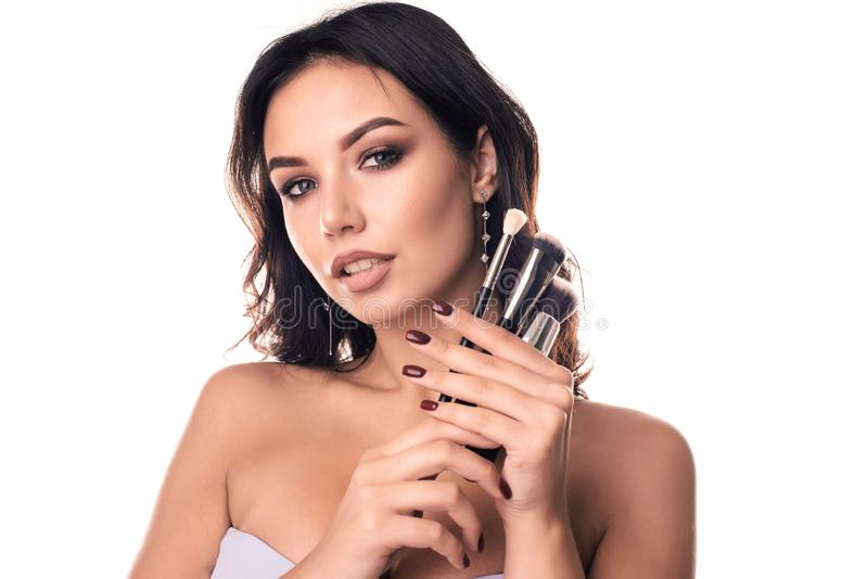Beauty Girl with Makeup Brushes. Natural Make-up for Brunette Woman with Brown Eyes royalty free stock photo