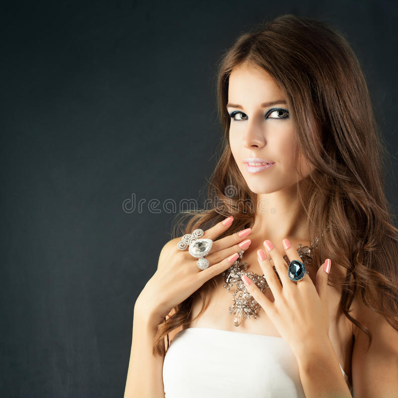 Beauty Girl. Makeup, Manicure Nails and Jewelry. Woman with Curly Hair and Bright Makeup royalty free stock images