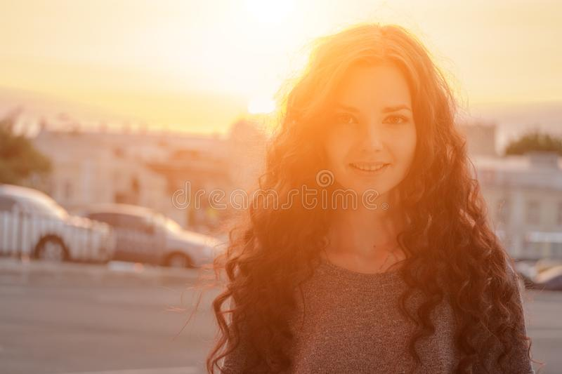 Beauty Girl Outdoors enjoying city evening time. Beautiful Teenage Model girl with long hair in Glowing Sun. Free Happy stock image