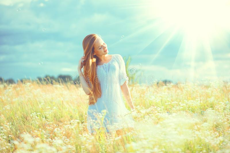 Beauty girl outdoors enjoying nature. Beautiful teenage model girl with healthy long hair in white dress. Standing on the summer field stock photos
