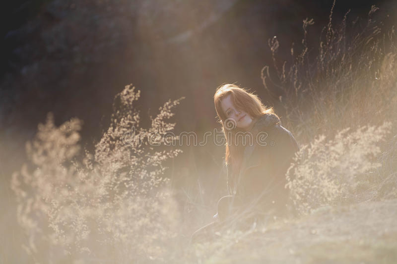 Beauty Girl Outdoors enjoying nature. Beautiful Teenage Model girl with long healthy blowing hair running on the Spring Field, Sun royalty free stock photography