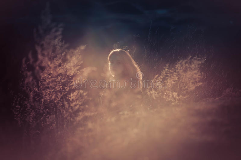 Beauty Girl Outdoors enjoying nature. Beautiful Teenage Model girl with long healthy blowing hair running on the Spring Field, Sun. Light. Glow Sun. Free Happy royalty free stock photo