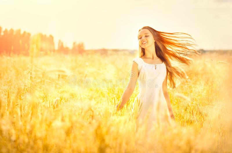 Beauty girl outdoors enjoying nature. Beautiful teenage model girl with healthy long hair in white dress. Standing on the summer field stock photography