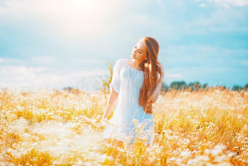 Beauty girl outdoors enjoying nature. Beautiful teenage model girl with healthy long hair in white dress. Standing on the summer field stock images