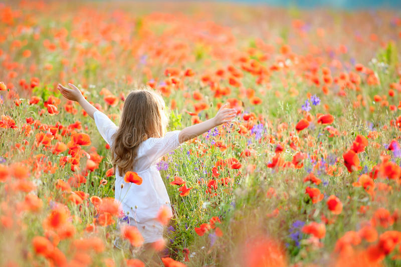 Beauty Girl Outdoors enjoying nature. Beautiful Teenage Model kid in white dress having fun on summer Field with blooming flowers royalty free stock photos