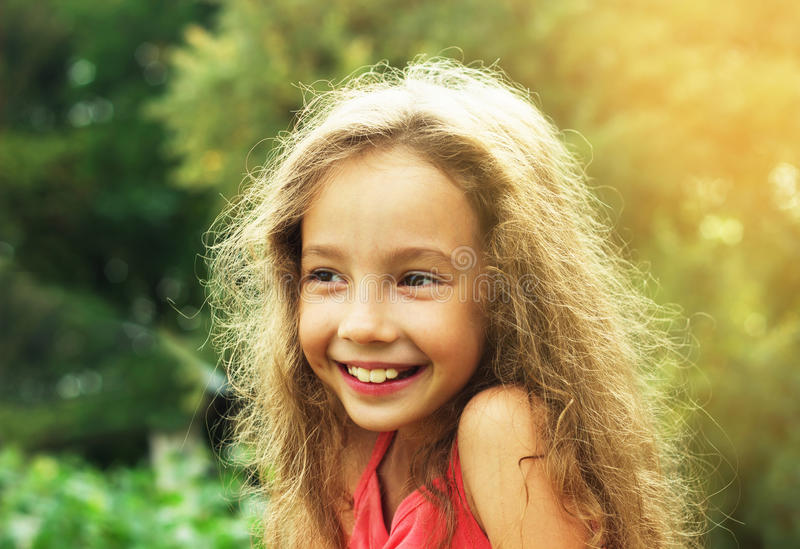 Beauty Girl Outdoors enjoying nature at sunset. Beautiful Teenage girl with long hair smiling. Happy kid. Toned in warm colors royalty free stock photos