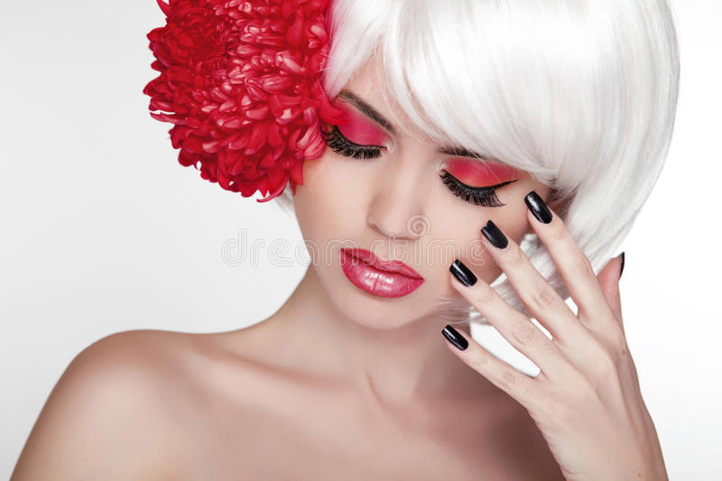 Beauty girl Portrait with red flower. Beautiful Spa Woman Touching her Face. Make up and manicured nails. Perfect Fresh Skin. stock photo