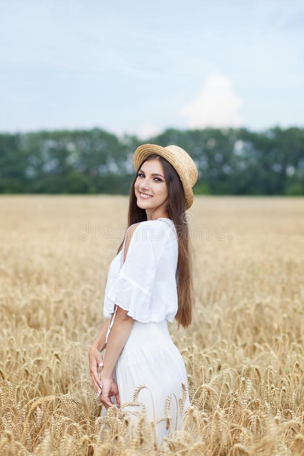 Beauty girl portrait in wheat field at sunset. Attractive young woman smiling and enjoying life. Beautiful brunette with a healthy royalty free stock image