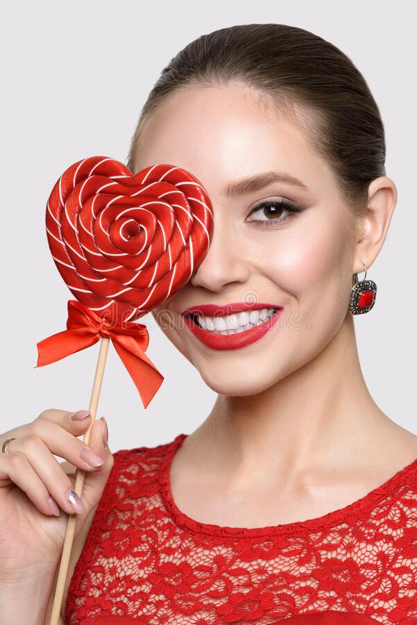 Beauty girl with a red lollipop in shape love heart, isolated on a white background royalty free stock images