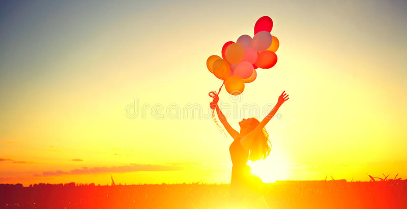 Beauty girl running and jumping on summer field with colorful air balloons. Over clear sky royalty free stock image