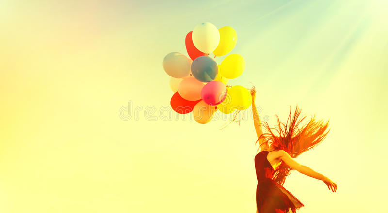 Beauty girl running and jumping on summer field with colorful air balloons royalty free stock photos