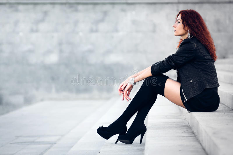 Beauty girl sits on a concrete steps. Beauty girl with red hair sitting on concrete steps royalty free stock photo