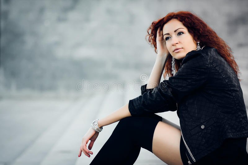 Beauty girl sits on a concrete steps. Beauty girl with red hair sitting on concrete steps and looks into the distance stock images