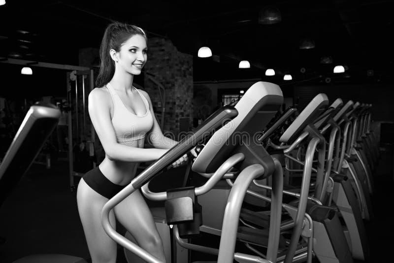 Beauty girl workout exercise on elliptic bike stock photography