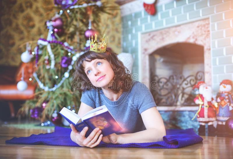 Beauty glamor Woman celebrating Christmas, reading a book wearing a dress and crown, festive Christmas background with royalty free stock photo