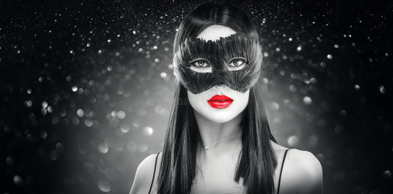 Beauty glamour brunette woman wearing carnival feather dark mask, party over holiday black background stock photo