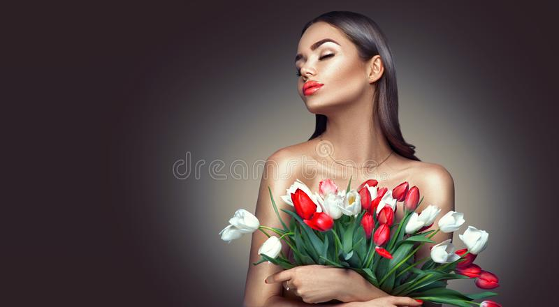 Beauty glamour girl with spring tulip flowers. Beautiful young woman with a Bunch of colorful Tulip flowers stock photography