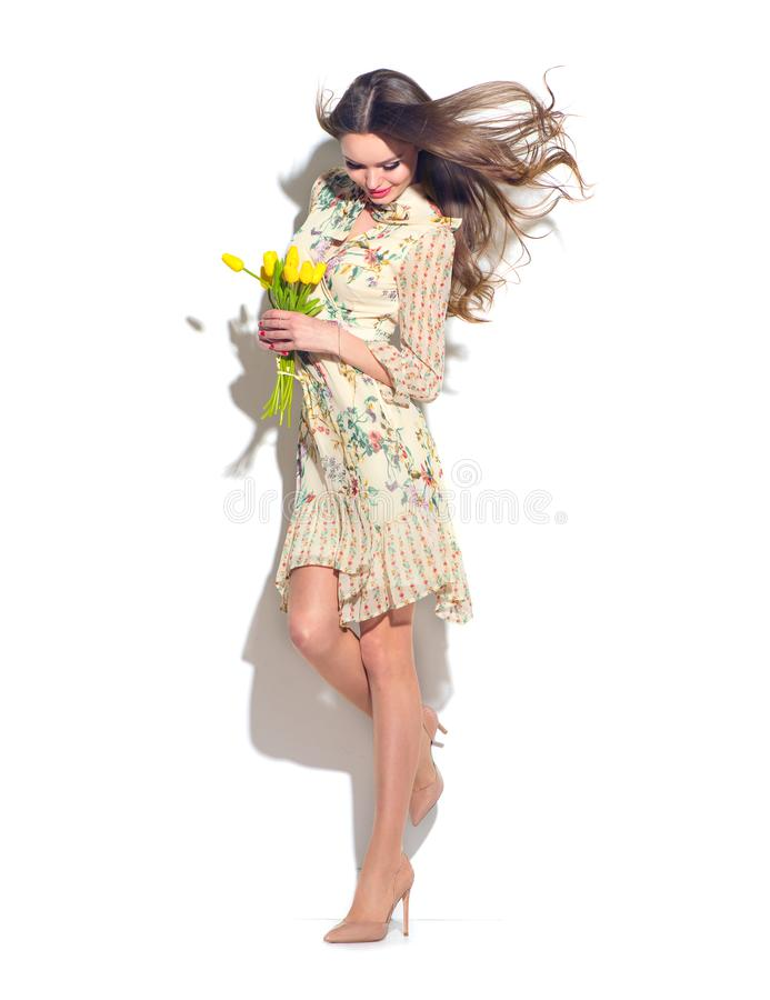Beauty glamour girl with spring tulip flowers. Beautiful young woman posing with bouquet of tulips. Model wearing chiffon dress royalty free stock image