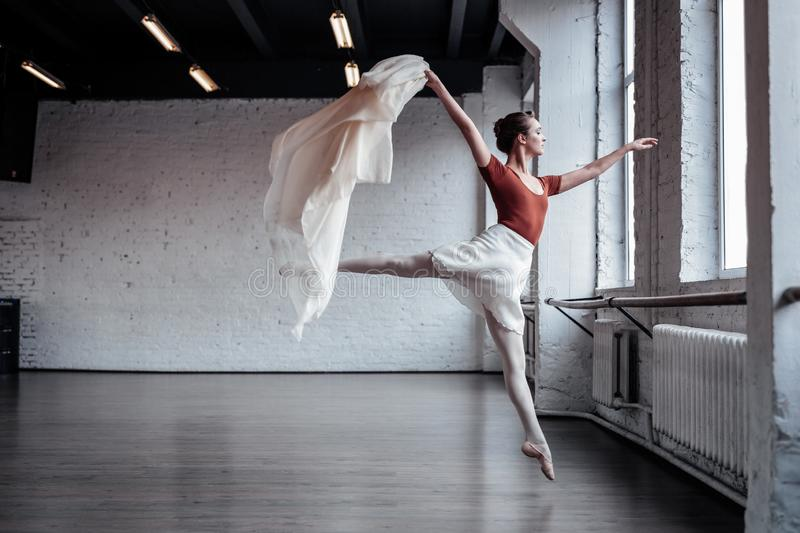 Attractive slim ballet dancer jumping during the dance. Beauty and grace. Attractive slim ballet dancer showing her grace while jumping during the dance royalty free stock images